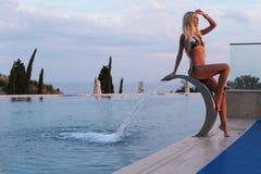 Sexy woman with blond hair in elegant bikini posing near luxurio Royalty Free Stock Photo