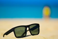 Fashion sunglasses on sea beach. Summer holiday relax background with copy space.  Royalty Free Stock Images
