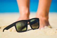 Fashion sunglasses on sea beach. Summer holiday relax background with copy space.  Stock Image