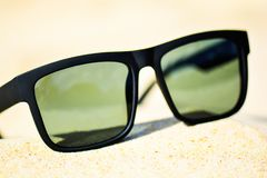 Fashion sunglasses on sea beach. Summer holiday relax background.  Stock Images