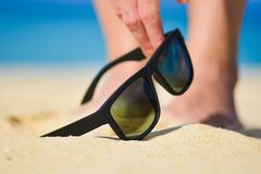 Fashion sunglasses on sea beach. Summer holiday relax background. Hand picking up sunglasses on the beach.  Royalty Free Stock Images