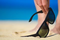 Fashion sunglasses on sea beach. Summer holiday relax background. Hand picking up sunglasses on the beach.  Stock Photo