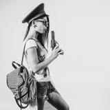 Fashion swag girl blowing on smoke toy gun woman having fun wearing police cap. Fashion swag girl blowing on smoke toy gun woman having fun wearing police cap royalty free stock images