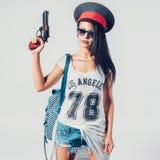 Fashion swag girl holding toy gun woman. Having fun wearing police cap royalty free stock photo