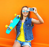 Fashion and technology concept - stylish young girl in colorful Stock Image