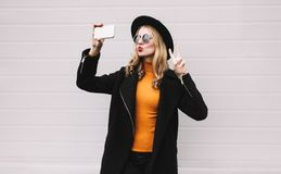 Fashion, technology and people concept - cool girl taking selfie picture by smartphone,. Elegant female model blowing red lips sends an air kiss posing in city stock photos