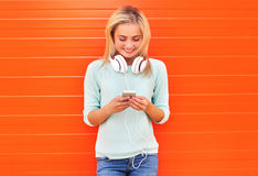 Fashion, technology and people concept - pretty smiling girl. Using smartphone in headphones against the colorful orange wall Royalty Free Stock Images