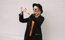 Stylish smiling woman taking selfie picture by smartphone,. Fashion, technology and people concept - stylish smiling woman taking selfie picture by smartphone stock photos
