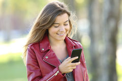 Fashion teen chatting on line with a mobile phone. Fashion teen wearing red jacket chatting on line with a mobile phone walking in a park Stock Images