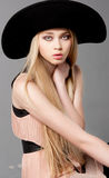 Fashion teen model in a black big hat. In studio Royalty Free Stock Photo