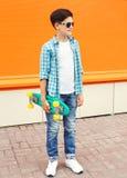 Fashion teenager boy wearing a shirt, sunglasses and skateboard Stock Image