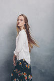 Fashion teenager girl standing against blue textured grunge wall background. Stock Photos
