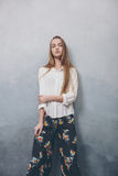 Fashion teenager girl standing against blue textured grunge wall background. Royalty Free Stock Image