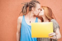 Fashion teenagers couple kissing and holding frame at red background Royalty Free Stock Images