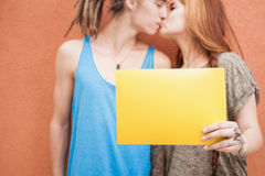 Fashion teenagers couple kissing and holding frame at red background Stock Image