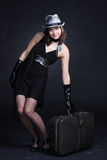 Fashion travel. Fashion cheerful young woman with trunk, isolated on black background Royalty Free Stock Images