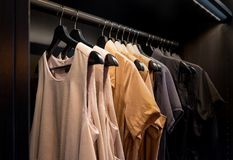 Fashion trend concept. Working lady clothes collection in dark w. Fashion trend concept. Working lady clothes collection hanging on a rack in dark wooden closet stock photos
