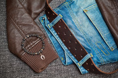 Fashion trend: jeans, leather jacket, leather belt, bracelet on the arm Royalty Free Stock Image