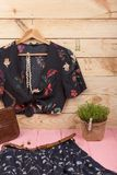 Fashion trends - black crop top / blouse in floral print on hangs on hanger, blue skirt, belt, bag and jewelry: hair pearl clip,. Necklace, earrings on wooden stock photo