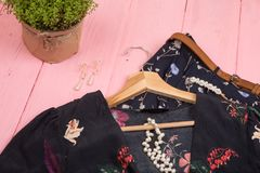 Black crop top / blouse in floral print on hangs on hanger, blue skirt, belt and jewelry: hair pearl clip, necklace, earrings on. Fashion trends - black crop top stock image