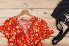 Fashion trends - black eco tote bag, dress in floral print on hanger and pearl jewelry: necklace, hair pearl clip, earrings. On wooden desk, background, red stock photo
