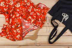 Fashion trends - black eco tote bag, dress in floral print on hanger and pearl jewelry: necklace, hair pearl clip, earrings. On wooden desk, background, red stock photography