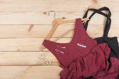 Fashion trends - black eco tote bag, red dress in polka dots on hanger and pearl jewelry: necklace, hair pearl clip, earrings. On wooden desk, background royalty free stock photos