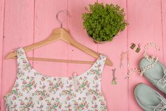 Fashion trends - dress in floral print on hangs on hanger, blue shoes and jewelry: pearl necklace, silver earrings. On pink wooden background, garment, white royalty free stock photo
