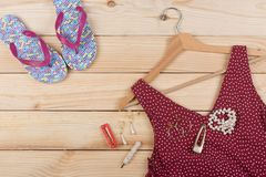 Fashion trends - flip flops, red dress in polka dots on hanger and jewelry: pearl necklace, hair pearl clip, earrings. On wooden desk, background, garment stock photography