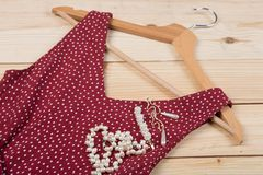 Fashion trends - red dress in polka dots on hanger and pearl jewelry: necklace, hair pearl clip, earrings. On wooden desk, background, garment, hairpin, shop stock image