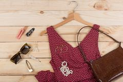 Fashion trends - sunglasses, bag, red dress in polka dots on hanger and jewelry: pearl necklace, hair pearl clip, earrings. On wooden desk, background, garment royalty free stock photos