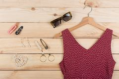 Fashion trends - sunglasses, red dress in polka dots on hanger and jewelry: pearl necklace, hair pearl clip, earrings stock images