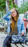 Fashion trendy casual young woman wearing a jean jacket and black leggings, sitting in a public chair, worried and. Touching her head like she is missing Royalty Free Stock Photography