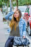 Fashion trendy casual young woman wearing a jean jacket and black leggings, sitting in a public chair, worried and. Touching her head like she is missing Stock Photo