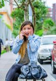Fashion trendy casual young woman wearing a jean jacket and black leggings, using her cellphone and showing shock Royalty Free Stock Photos