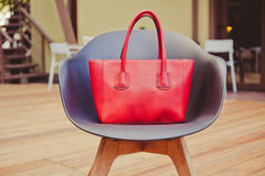 Fashion and trendy style large red handbag designer stands on a beautiful chair made of plastic in a summer cafe in the Royalty Free Stock Image