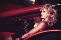 Fashion on truck. Blond fashion model in punk style clothes and hair pose on truck night shot Stock Photo