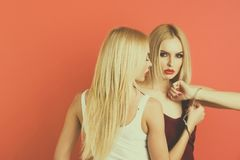 Fashion twin girls or beautiful women friends with blonde hair. Fashion twin girls in handcuff or beautiful women friends with blonde hair on pink background royalty free stock photography
