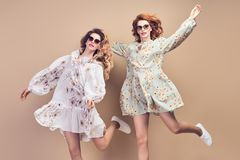 Fashion. Two happy woman jumping dance Having Fun. Fashion. Two Inspired happy women smiling jump in Studio. Excited sister friend Having Fun, Stylish stock images