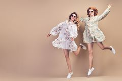 Fashion. Two happy woman jumping dance Having Fun. Fashion. Two happy women smiling jump in Studio. Easy-going comic sister friend Having Fun, Stylish stock photography