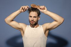 Fashion, underwear, style. Macho with bearded face and haircut in white singlet. Fashion, underwear, style. Man brush hair with hairbrush on blue background royalty free stock photo