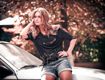 Fashionable woman posing outdoor in the city near a car Stock Images