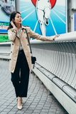 Fashion urban young woman living city lifestyle. Full length of fashion urban young woman living city lifestyle walking in coat on the bridge crossing river in stock photo