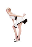 Fashion victim. Pretty long-legged blond in stylish dress and shoes bending with black purse in hand Stock Photo