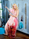 Fashion vintage blond housewife cleaning mop. Fashion vintage blond housewife with mop cleaning chores at home Stock Photo