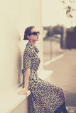 Fashion vintage style - beautiful elegant woman in leopard dress. And sunglasses outdoors Stock Image