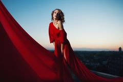 Fashion vogue style portrait of young stunning woman posing in red dress in sunset royalty free stock photos