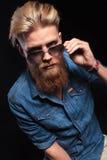 Fashion wearing blue shirt, pulling his sunglasses Stock Photography