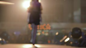 Fashion Week, silhouette professional podium model into dress walk on catwalk in backlight in unfocused during