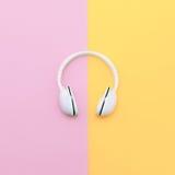 Fashion white headphones on vanilla background